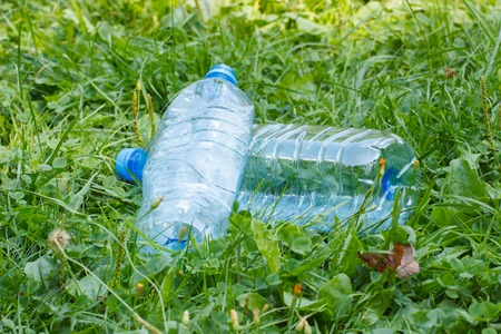 littering: Plastic bottles of mineral water on grass in sunny park, concept of environmental protection, littering of environment