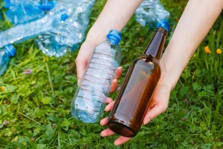 botar basura: Mano de la mujer con el plástico y botellas de vidrio, el concepto de protección del medio ambiente, tirar basura del entorno Foto de archivo