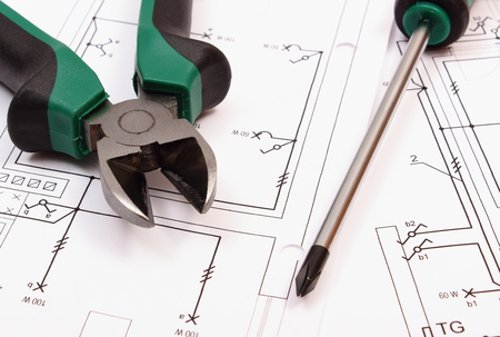 Orange metal pliers with rolled electrical diagram lying on metal pliers and screwdriver on electrical construction drawing of house work tool and drawing for ccuart Gallery