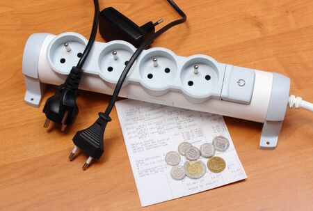 electricity prices: Electrical plugs with cords disconnected from electrical power strip, electricity bill with heap of coins, concept of energy saving Stock Photo