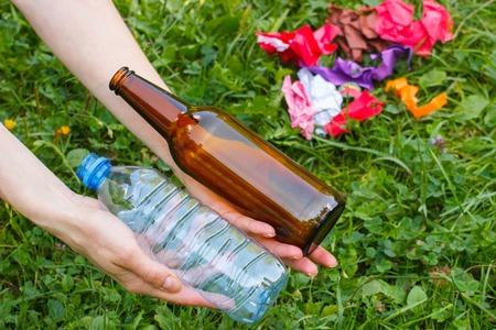 tirar basura: Mano de la mujer con el pl�stico y botellas de vidrio, basura en hierba en el fondo, el concepto de protecci�n del medio ambiente, tirar basura del entorno