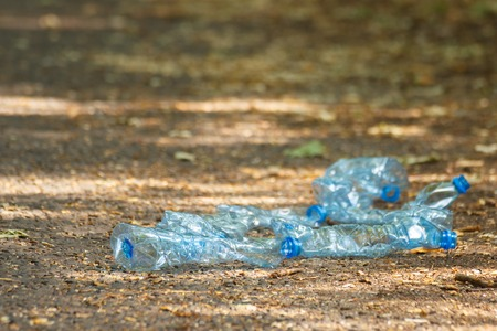 tirar basura: botellas aplastadas de pl�stico de agua mineral en el camino en el parque, el concepto de protecci�n del medio ambiente, tirar basura del entorno