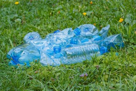 botar basura: Botellas de plástico triturado de agua y tapas de botellas de minerales en el césped en el parque, el concepto de protección del medio ambiente, basura del medio ambiente Foto de archivo