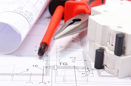 ingeniero electrico: Rollos de diagramas eléctricos, fusibles eléctricos y herramientas de trabajo que mienten en el dibujo de la construcción de la casa, dibujos para los trabajos de proyectos de ingeniería