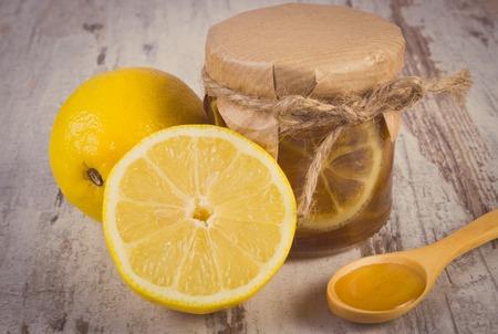 inmunidad: Foto de la vendimia, Frasco de vidrio con lim�n y miel, lim�n y miel en la cuchara de madera situada en la vieja mesa de madera blanca, la comida sana y el fortalecimiento de la inmunidad