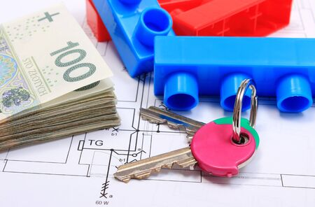 red building blocks: Heap of banknotes, home keys and plastic colorful building blocks lying on construction drawing of house