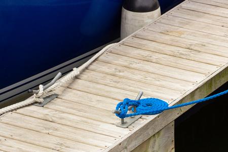 mooring bollard: Yachting, blue rope and mooring bollard on bridge in port of sailing Stock Photo