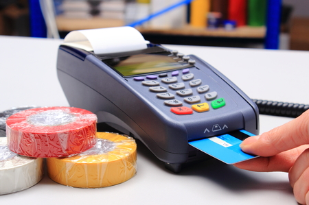 credit card reader: Hand of woman using payment terminal in an electrical shop, paying with credit card Stock Photo