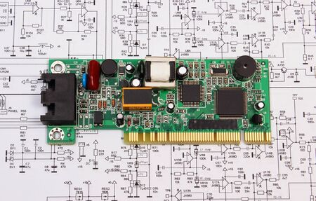 printed: Printed circuit board with electrical components lying on construction drawing of electronics