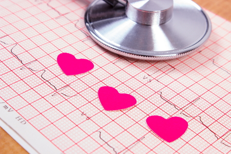 amplitude: Hearts of paper and medical stethoscope lying on electrocardiogram graph, ecg heart rhythm, medicine and healthcare concept