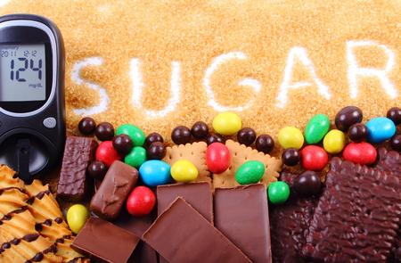 diabetes: Medidor de glucosa, natural granulada de caña de azúcar de color marrón y un montón de caramelos y galletas, el concepto de demasiados dulces, comida poco saludable y la diabetes
