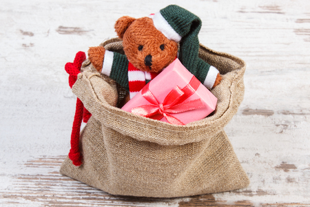 juguetes antiguos: Teddy bear and wrapped colorful gifts for Christmas, birthday, valentines or other celebration in jute bag on old wooden white table Foto de archivo