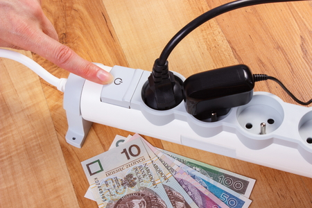 energy costs: Finger of woman turns off electrical power strip with connected plug, polish currency money, concept of saving money on electricity, energy costs Stock Photo
