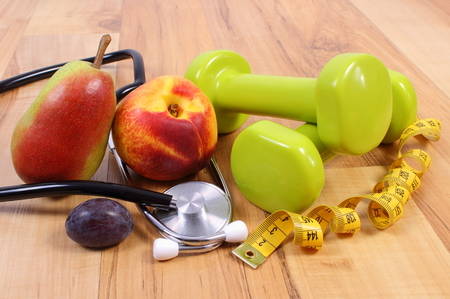 stethoscope: Medical stethoscope, fruits and dumbbells for using in fitness, concept of health care, healthy lifestyles and nutrition
