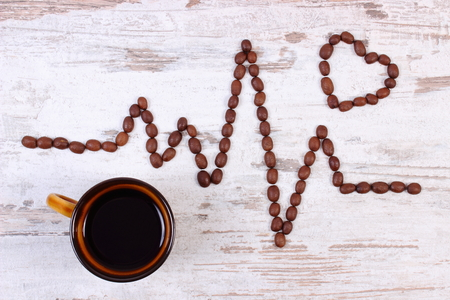 ecg heart: Electrocardiogram line of roasted coffee grains and cup of hot coffee on rustic wooden background, ecg heart rhythm, medicine and healthcare concept Stock Photo