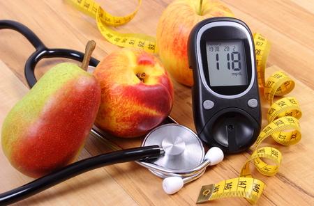 diabetes: Medidor de glucosa con el estetoscopio m�dico y frutas frescas, el concepto de la diabetes, estilos de vida saludables y la nutrici�n Foto de archivo