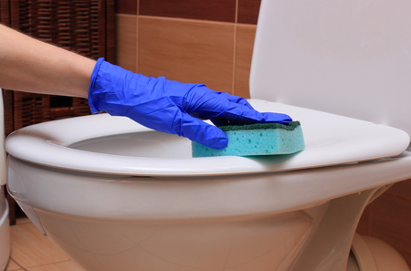 woman on toilet: Hand of woman in blue glove cleaning toilet bowl, concept of house cleaning and household duties