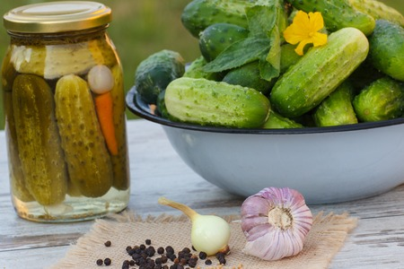 pickling: Ripe cucumbers in metal bowl, spices for pickling and jar marinated cucumbers on old wooden white table in garden on sunny day, food and nutrition Stock Photo