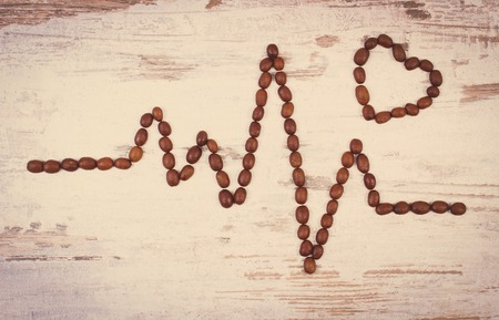 ecg monitoring: Vintage photo, Electrocardiogram line of roasted coffee grains on rustic wooden background, ecg heart rhythm, medicine and healthcare concept
