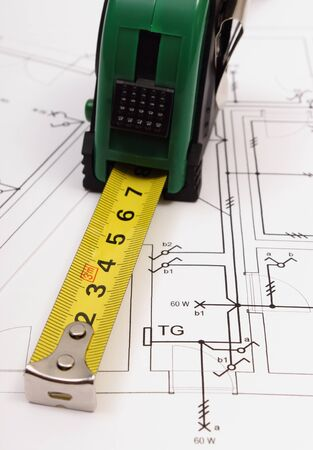 housing project: Tape measure on electrical construction drawing of house, work tool and drawing for projects engineer jobs, concept of building house
