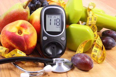 Glucosemeter met medische stethoscoop, fruit en halters voor gebruik in fitness, concept van diabetes, een gezonde levensstijl en voeding Stockfoto