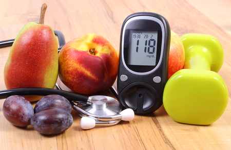 healthcare and  medicine: Glucose meter with medical stethoscope, fruits and dumbbells for using in fitness, concept of diabetes, healthy lifestyles and nutrition