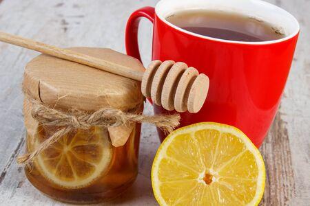 inmunidad: Lim�n con miel en frasco de vidrio, lim�n fresco y una taza de t� caliente en la vieja mesa de madera blanca, alimentos saludables, fortalecer la inmunidad y la terapia alternativa