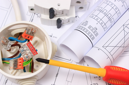 Koperdraad aansluitingen in elektrische doos, rollen van elektrische schema's en elektrische zekering op de bouw tekening van huis, accessoires voor engineering, energie-concept Stockfoto