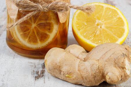 limón: Limón con miel en frasco de vidrio, limón y jengibre en mesa de madera vieja, el concepto de la comida sana, la nutrición y el fortalecimiento de la inmunidad