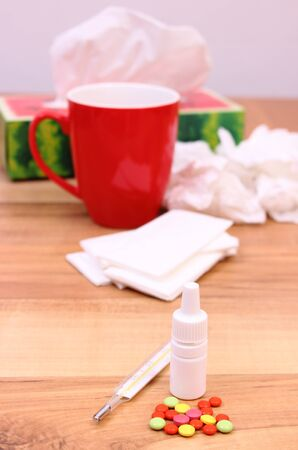 handkerchiefs: Pills and nose drops for colds, used handkerchiefs and hot tea with lemon in background, treatment of colds, flu and runny