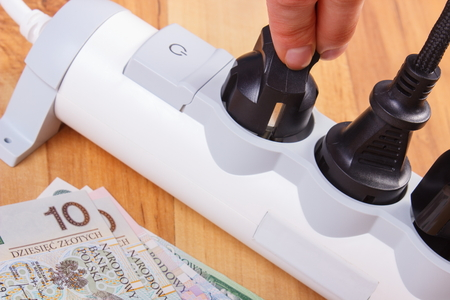 energy costs: Hand of woman turns off plug from electrical extension, polish currency money, concept of saving money on electricity, energy costs Stock Photo