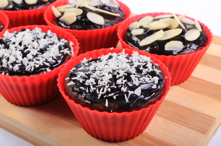 desiccated: Homemade delicious fresh baked chocolate muffins with desiccated coconut and sliced almonds in red silicone cups lying on wooden cutting board, concept for dessert
