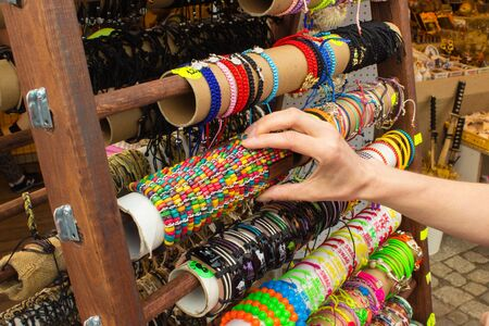 ladylike: Hand of woman with colorful bracelets, shopping jewelry and womanly accessories on stall at the bazaar Stock Photo