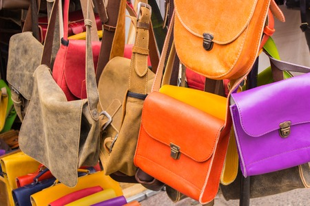 Collection of handmade leather handbags on stall at the bazaar, womanly accessories