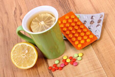 gripe: Píldoras y té caliente con limón para los resfriados, el tratamiento de los resfriados, la gripe y que moquea Foto de archivo