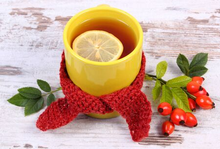 Cup of tea with lemon wrapped woolen scarf and bunch of wild rose with leaves, warming beverage for flu and cold, autumn composition