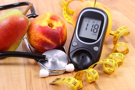 diabetes: Glucose meter with medical stethoscope and fresh fruits, concept of diabetes, healthy lifestyles and nutrition