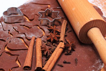 cookie cutters: Spice for baking, anise cinnamon sticks and cloves, cookie cutters on dough for Christmas cookies and gingerbread, concept of baking and Christmas time
