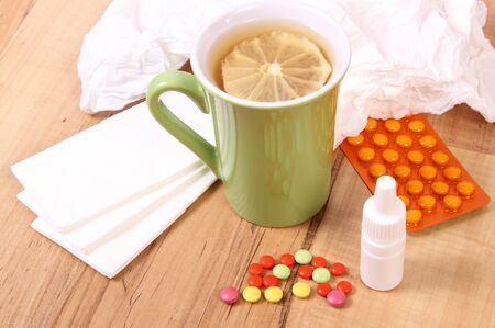 colds: Pills and nose drops for colds, handkerchiefs and hot tea with lemon, treatment of colds, flu and runny Stock Photo