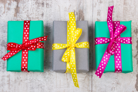 Wrapped colorful gifts for Christmas, birthday or other celebration on old wooden white plank 스톡 콘텐츠