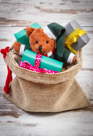 teddy bear love: Teddy bear and wrapped colorful gifts for Christmas, birthday, valentines or other celebration in jute bag on old wooden white table Stock Photo