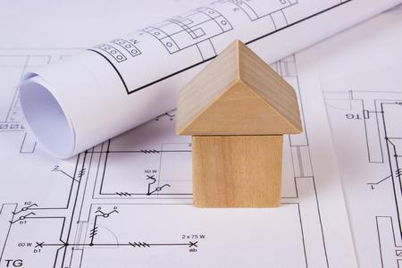 Hausform, Die Aus Holzklötzen Und Rollen Von Diagrammen Auf Elektrischen  Konstruktionszeichnungen Des Hauses Liegen,