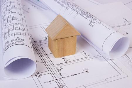 Hausform, Die Aus Holzklötzen Und Rollen Von Diagrammen Auf Elektrischen  Konstruktionszeichnungen Des Hauses Liegen, Das Konzept Von Haus Zu Bauen,  ...