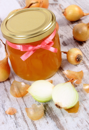 immunity: Fresh organic honey in glass jar and onions on old rustic wooden background, healthy nutrition, strengthening immunity and treatment of colds and flu Stock Photo