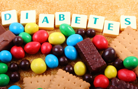 Heap of sweet candies and cookies with brown cane sugar and word diabetes, unhealthy food, concept of diabetes and reduction of eating sweets