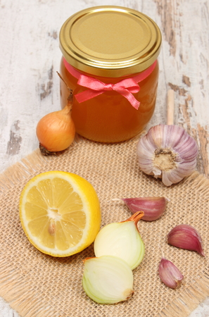 inmunidad: Fresh organic onion, garlic, lemon and honey in glass jar on old wooden background, healthy nutrition, strengthening immunity and treatment of flu Foto de archivo