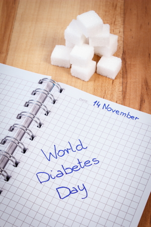 medical fight: Inscription World diabetes day in notebook and sugar cubes, symbol of diabetic and fight against diabetes Stock Photo
