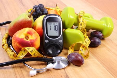 nutrición: Medidor de glucosa con el estetoscopio médicos, frutas y pesas para usar en la aptitud, el concepto de la diabetes, estilos de vida saludables y la nutrición Foto de archivo
