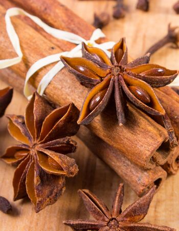 stick of cinnamon: Star of anise, cinnamon sticks and cloves lying on wooden table, seasoning for cooking and baking