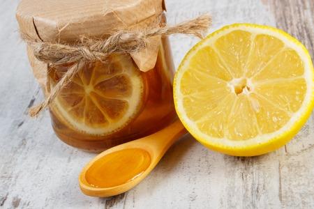 inmunidad: Frasco de vidrio con lim�n y miel, lim�n y miel en la cuchara de madera situada en la vieja mesa de madera blanca, el concepto de la comida sana, la nutrici�n y la inmunidad fortalecimiento